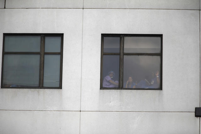 <p>Those still inside the building peek out the windows after a shooting killing one and wounding six others at Bronx Lebanon Hospital Center Friday, June 30, 2017, in New York. (AP Photo/Michael Noble) </p>