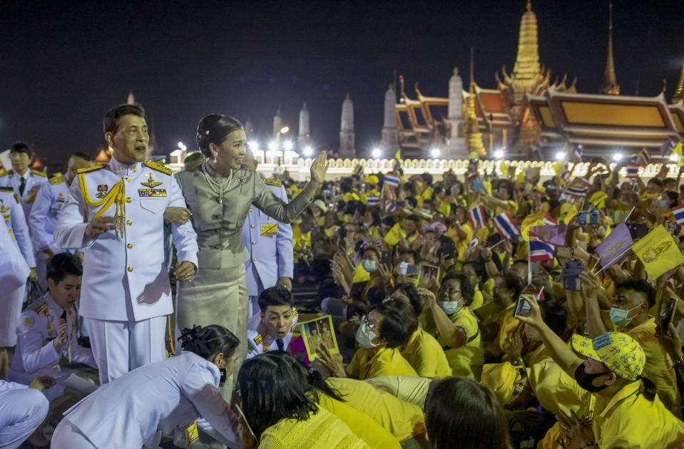 King Maha Vajiralongkorn, left and Queen Suthida, right wave to supporters in Bangkok, Thailand, Sunday, Nov. 1, 2020. Under increasing pressure from protesters demanding reforms to the monarchy, Thailand's king and queen met Sunday with thousands of adoring supporters in Bangkok, mixing with citizens in the street after attending a religious ceremony inside the Grand Palace. (AP Photo/Wason Wanichakorn)