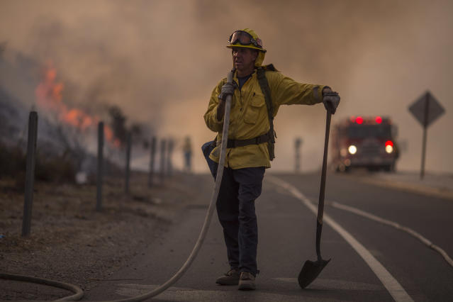 <p>A firefighter holds a hose on the 120 freeway during the La Tuna fire on Sept. 2, 2017 near Burbank, Calif. (Photo: David McNew/Getty Images) </p>