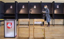 A local resident walks to cast a ballot at a polling station during the second round of a parliamentary election in Vilnius, Lithuania, Sunday, Oct. 25, 2020. Polls opened Sunday for the run-off of national election in Lithuania, where the vote is expected to bring about a change of government following the first round, held on Oct. 11, which gave the three opposition, center-right parties a combined lead. (AP Photo/Mindaugas Kulbis)