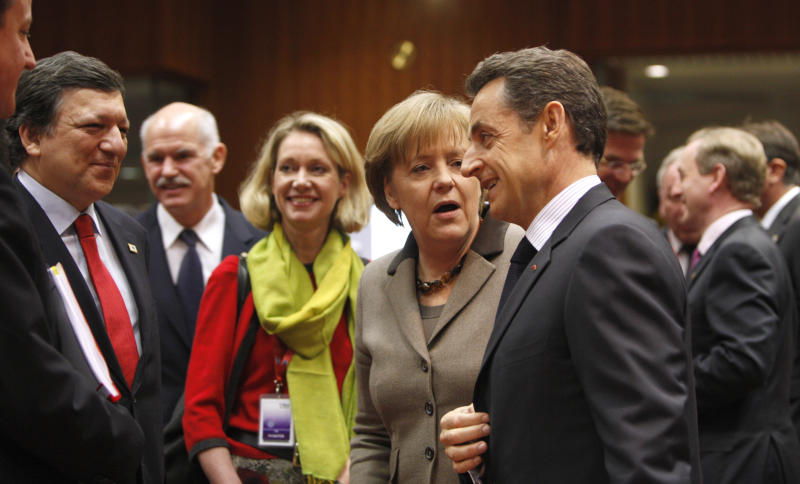 German Chancellor Angela Merkel, center right, speaks with French President Nicolas Sarkozy, fifth right, during a round table meeting at an EU Summit in Brussels on Friday, March 11, 2011. European Union nations are putting French President Nicolas Sarkozy under pressure even before his arrival at Friday's EU summit, complaining he was out of line to give a Libyan opposition group diplomatic recognition before any joint action could be discussed. Standing left is European Commission President Jose Manuel Barroso, and second left is Greek Prime Minister George Papandreou. (AP Photo/Virginia Mayo)