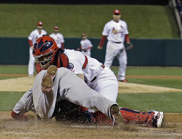 St. Louis Cardinals catcher Yadier Molina tags out Boston Red Sox's David Ross at home during the seventh inning of Game 5 of baseball's World Series Monday, Oct. 28, 2013, in St. Louis. Ross tried to score from second on a hit by Jacoby Ellsbury. (AP Photo/David J. Phillip)