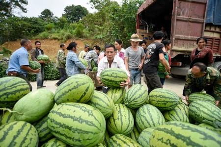 People load a truck with watermelons at a village in Qianxinan