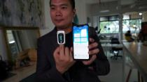Nervotec founder Jonathan Lau shows the comparison in vital signs readings between his company's app and a pulse oxygen monitor, in Singapore
