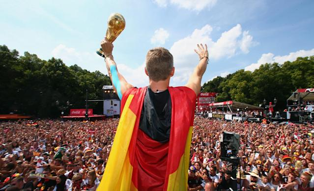 "German soccer player Bastian Schweinsteiger celebrates on stage at the German team victory ceremony , near the Brandenburg Gate in Berlin, Tuesday July 15, 2014. Germany's World Cup winners shared their fourth title with hundreds of thousands of fans by parading the trophy through cheering throngs to celebrate at the Brandenburg Gate on Tuesday. An estimated 400,000 people packed the ""fan mile"" in front of the Berlin landmark to welcome home coach Joachim Loew's team and the trophy which returned to Germany for the first time in 24 years. (AP Photo/ Alex Grimm,Pool)"