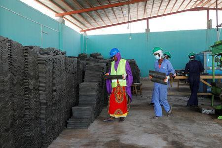 Employees carry roofing tiles made from recycled plastic litter at the Envirogreen recycling plant in Mogadishu, Somalia January 13, 2019. Picture taken January 13, 2019. REUTERS/Feisal Omar