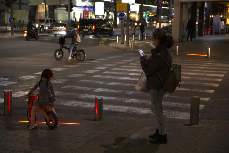 In this Wednesday, March 13, 2019 photo, Israeli pedestrians stand in front of embedded LED stoplights at a crosswalk in Tel Aviv, Israel. Tel Aviv has taken its first steps to assist pedestrians distracted by their smartphones by embedding LED stoplights at crosswalks. (AP Photo/Sebastian Scheiner)