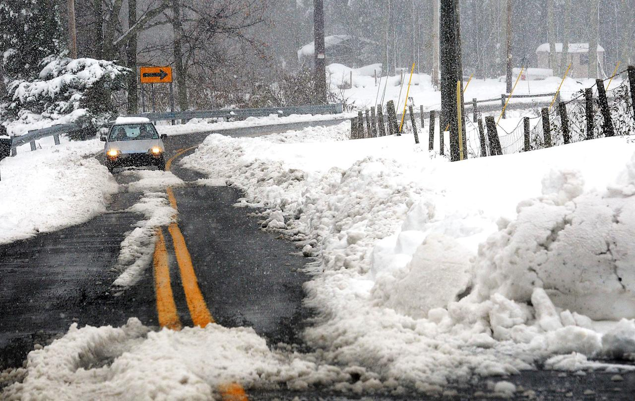 A car drives on a road in Beaver, W.Va., Wednesday, Oct. 31, 2012. Superstorm Sandy has already dumped up to 2 feet of snow in West Virginia, cutting electricity to about 271,00 customers and closing dozens of roads. (AP Photo/The Register-Herald, Rick Barbero)