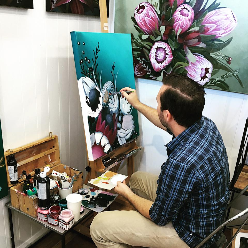 Australian painter Chris Riley seated while painting native flowers. Photo: supplied.