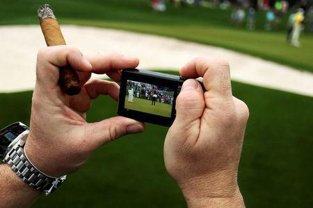A patron holds a lit cigar and a camera during the third day of practice rounds before The Masters at Augusta National Golf Club in Augusta, Georgia, U.S. April 5, 2017. REUTERS/Jonathan Ernst