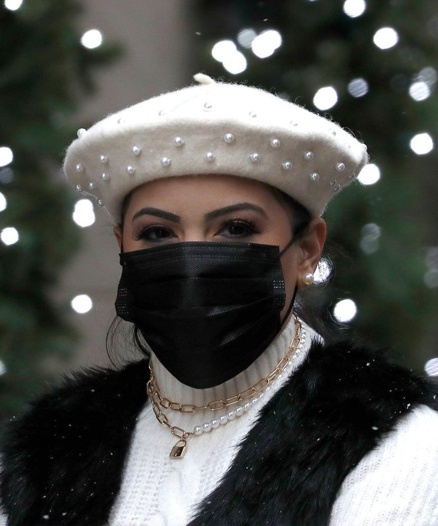 NEW YORK, NEW YORK – DECEMBER 09: A woman wearing a protective mask walks by Fifth Avenue holiday ornaments on December 9, 2020 in New York City. Many events for the holidays have been canceled or adjusted with additional safety measures due to the ongoing coronavirus (COVID-19) pandemic. (Photo by John Lamparski/Getty Images)