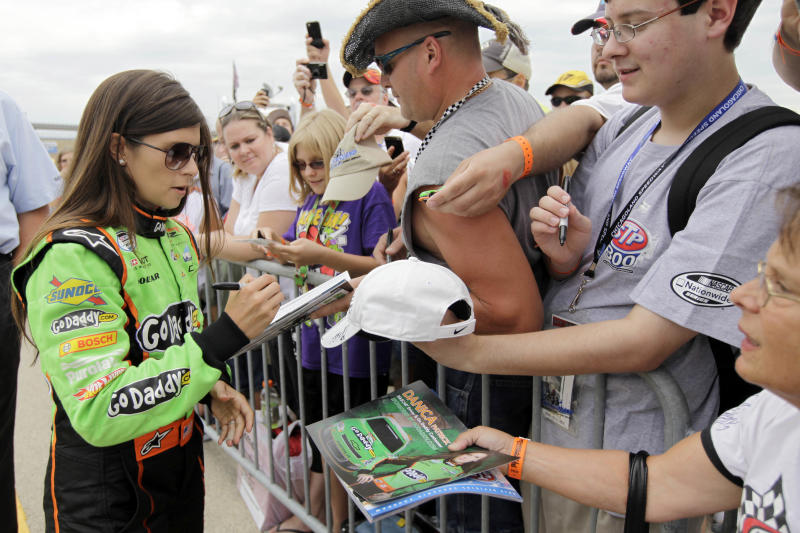 Danica Patrick, left, signs autographs for fans before the NASCAR Nationwide Series qualifying auto race at Chicagoland Speedway in Joliet, Ill., Sunday, July 22, 2012. (AP Photo/Nam Y. Huh)