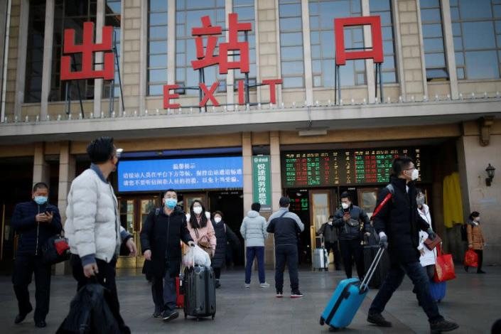 People wearing face masks carry their luggage outside Beijing Railway Station as the country is hit by an outbreak of the new coronavirus, in Beijing
