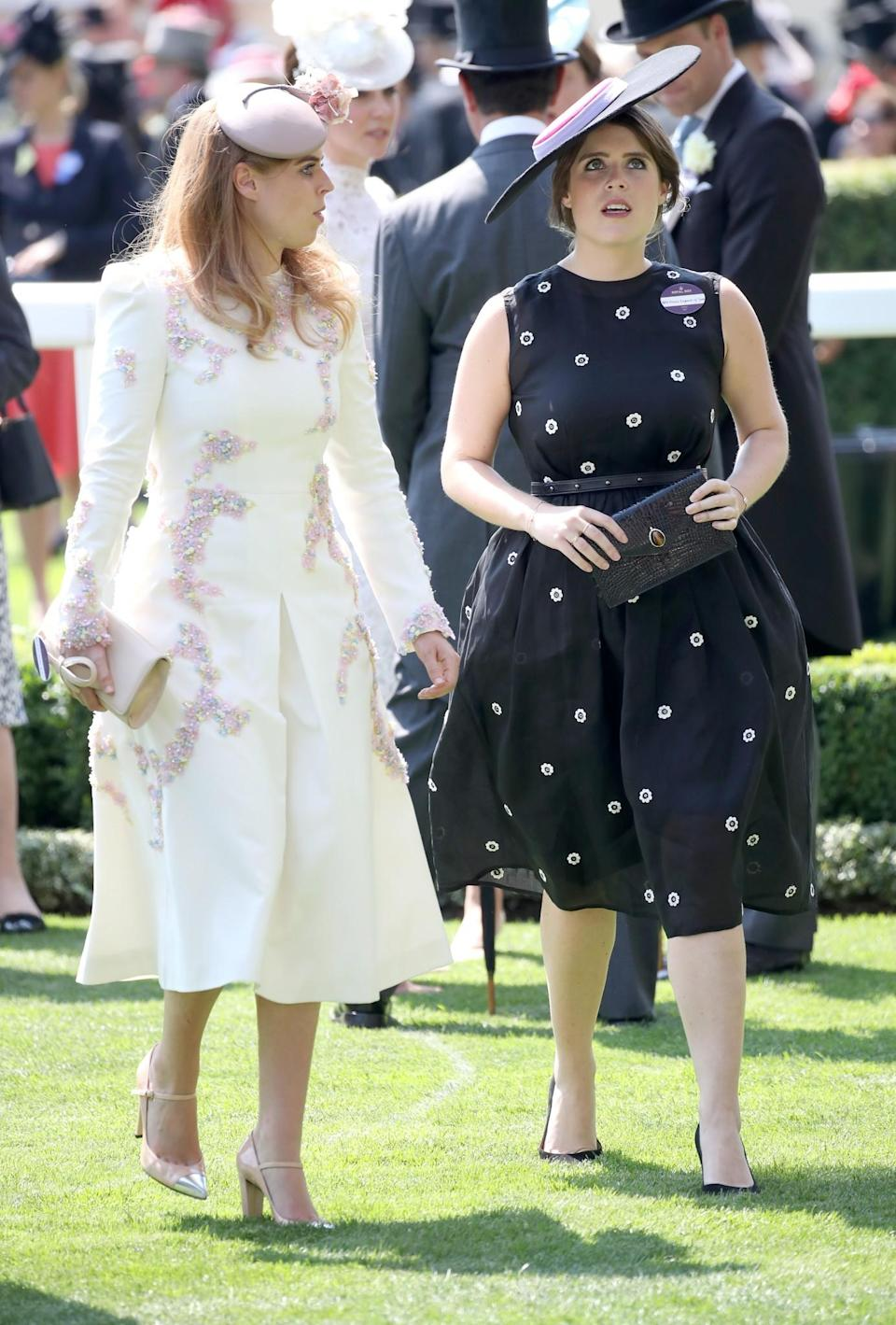 <p>The Princesses of York, known for their adventorous sense of style, arrived wearing rather modest outfits. Beatrice opted for a white, embellished dress while Eugenie went against the grain in a black dress teamed with a tricolour hat. <br><em>[Photo: Getty]</em> </p>