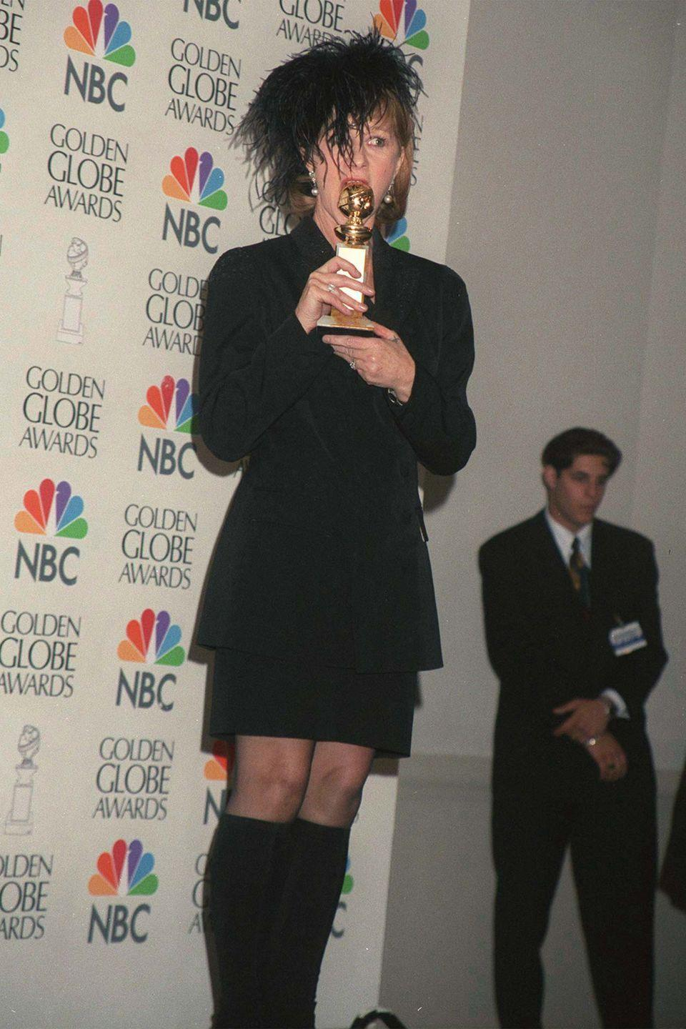 <p>A black skirt suit with knee-high boots and feathered headpiece was the look for the <em>Losing Chase </em>actress in 1997.</p>