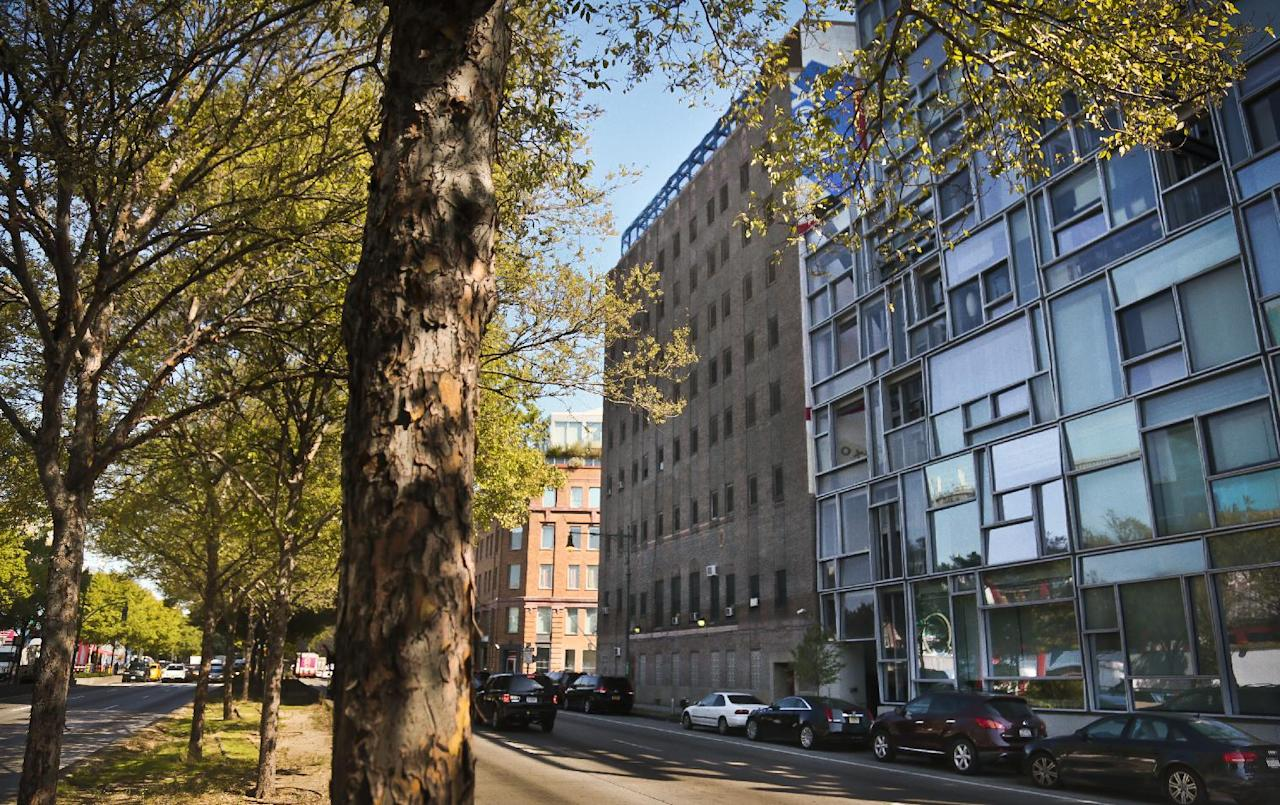 In this Sept. 30, 2013 photo shows a high rise condominium designed by French architect Jean Nouvel, right, is shown. The high rise is adjacent to the Bayview Correctional Facility, center, a minimum security women's prison in the Chelsea section of New York. The eight-story building, surrounded by upscale restaurants, luxury condos, high-end shops and steps away from the popular Highline elevated park, remains closed after damage during superstorm Sandy. (AP Photo/Bebeto Matthews)