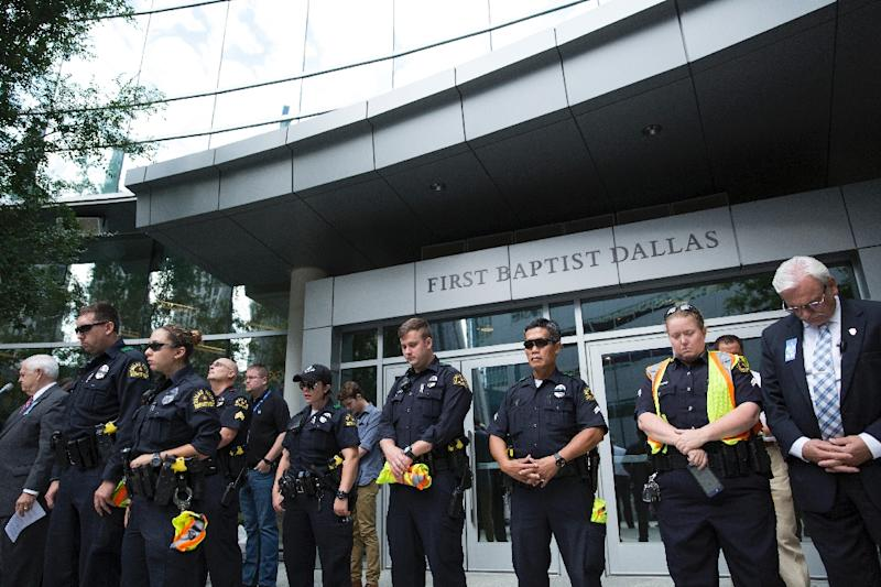 Police officers join parishioners of First Baptist Church in Dallas, Texas, as they gather on July 10, 2016, to pray for victims of the Dallas sniper attack (AFP Photo/Laura Buckman)