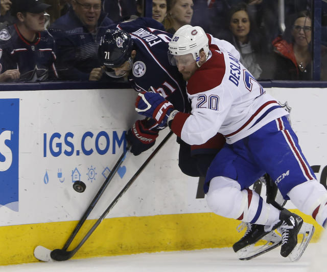 Montreal Canadiens' Nicolas Deslauriers, right, checks Columbus Blue Jackets' Nick Foligno during the second period of an NHL hockey game Thursday, March 28, 2019, in Columbus, Ohio. (AP Photo/Jay LaPrete)
