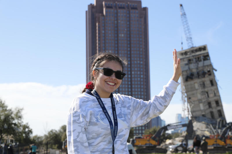 "Eloisa Alvarado poses for a photo as she and friends watch the demolition of the so called ""Leaning Tower of Dallas"" as a wrecking ball works to topple the structure north of downtown Dallas, Monday, Feb. 24, 2020. The still standing structure is part of an 11-story building that found a second life online after surviving a first demolition attempt. The former Affiliated Computer Services building inspired jokes and comparisons to Italy's Leaning Tower of Pisa when a Feb. 16 implosion failed to bring down its core. The company that engineered the blast said some explosives did not go off. (AP Photo/LM Otero)"
