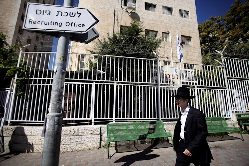 An Ultra Orthodox Jewish man walks past an army recruiting base in Jerusalem. Monday, July 2, 2012. Israel's prime minister on Monday dissolved a high-profile committee assigned to reform the country's military draft law to spread the burden among more sectors of society, conscripting ultra-Orthodox Jews and requiring Israeli Arabs to do civilian service. (AP Photo/Dan Balilty)