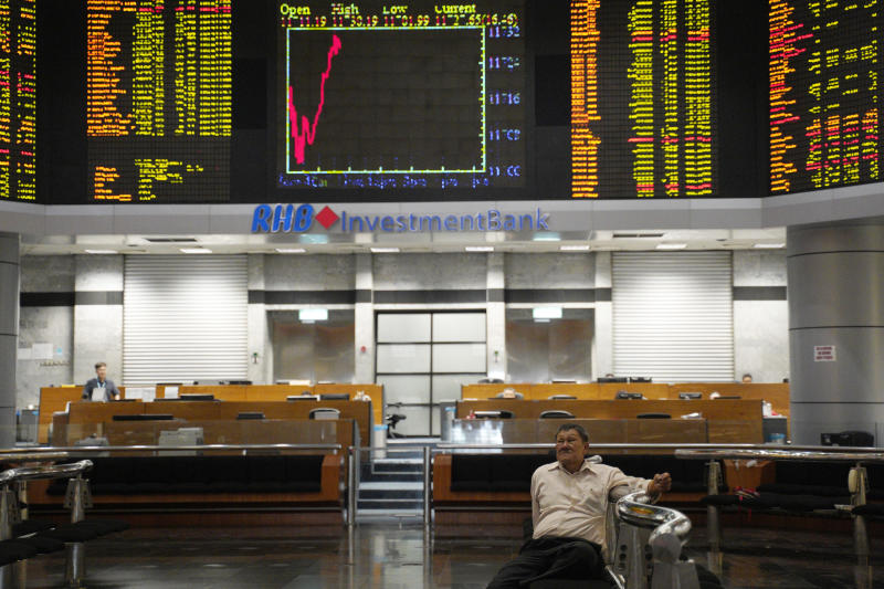 A visitor sits in front of private stock trading boards at a private stock market gallery in Kuala Lumpur, Malaysia, Friday, March 15, 2019. Shares were higher Friday in Asia after a day of lackluster trading on Wall Street. (AP Photo/Yam G-Jun)
