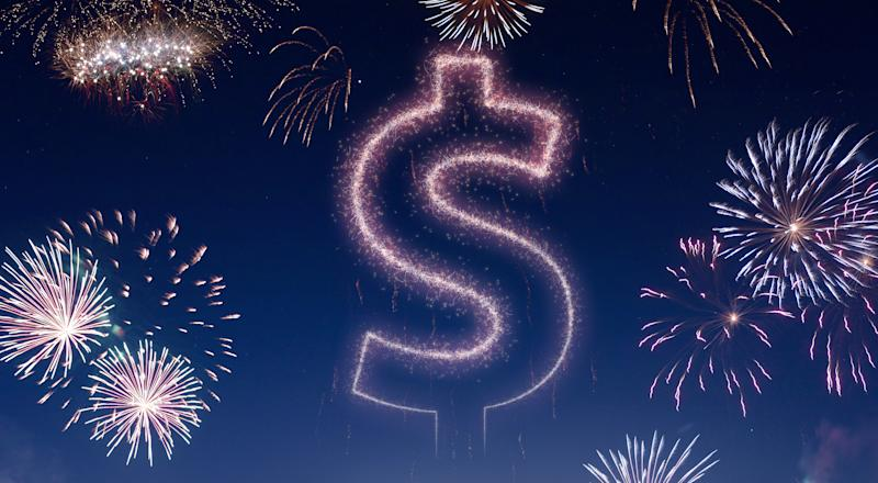 Nighttime fireworks show with a dollar sign in the sky