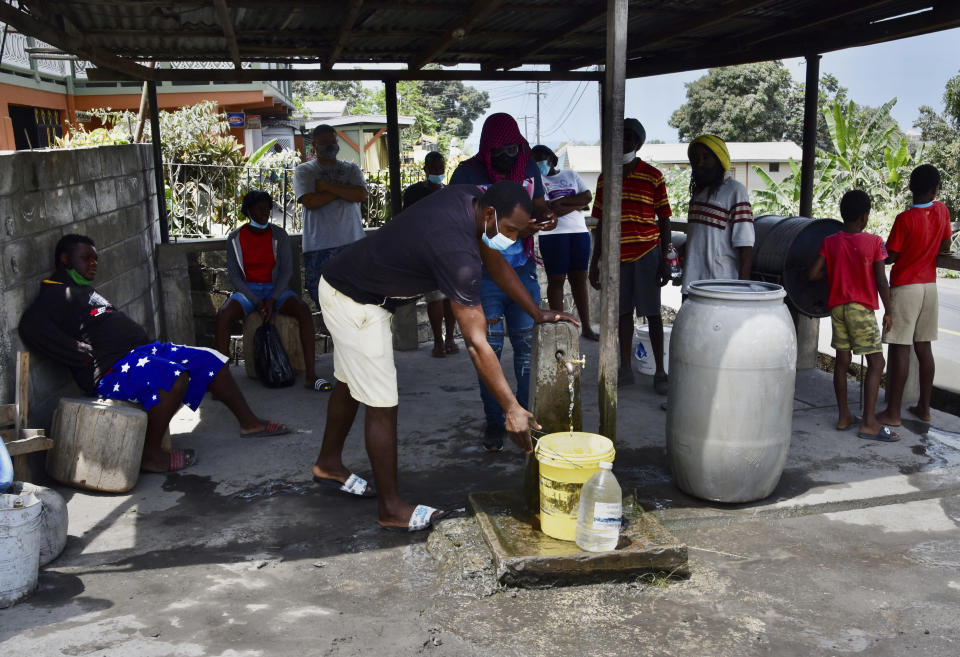 People collect water not contaminated by volcanic ash after the eruption of La Soufriere volcano in Wallilabou, on the western side of the Caribbean island of St. Vincent, Monday, April 12, 2021. (AP Photo/Orvil Samuel)