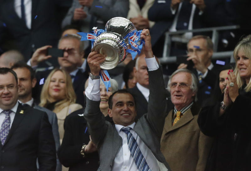Wigan Athletic's manager Roberto Martinez lifts up the trophy after their win against Manchester City at the end of their English FA Cup final soccer match at Wembley Stadium, London, Saturday, May 11, 2013. (AP Photo/Matt Dunham)