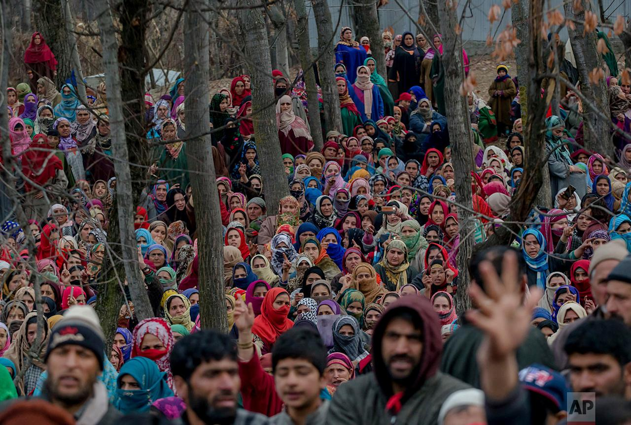 <p>Kashmiri villagers watch the funeral procession of Rayees Ahmed in Narapora, 55 Kilometers (35 miles) south of Srinagar, Indian controlled Kashmir Ahmed, died Wednesday in a hospital in Srinagar five days after he sustained gunshot wounds fired by Indian army soldiers that left two young men killed and nine others injured in a village in the disputed Himalayan region. (AP Photo/Dar Yasin) </p>