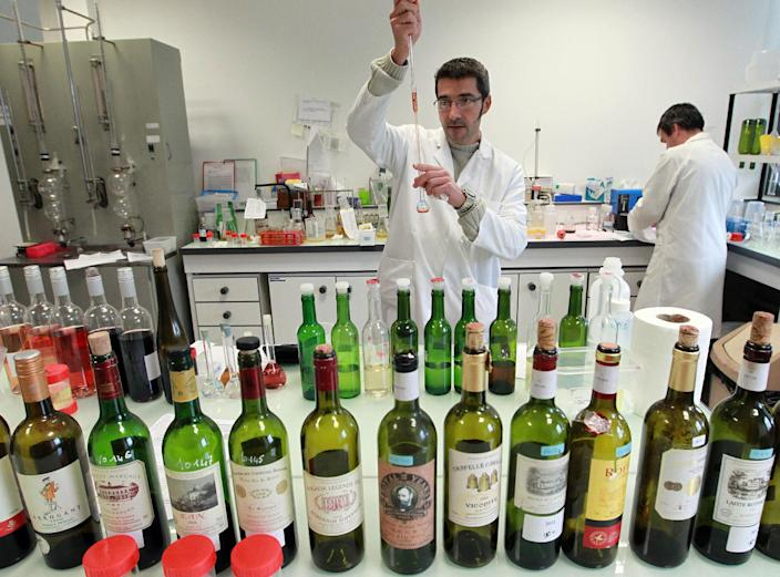 In this photo dated Tuesday, Nov. 12, 2013, an unidentified lab worker tests wine for authenticity in a lab run by the French Finance ministry in Bordeaux, southwestern France. Counterfeiting has dogged wine as long as it has been produced, but it is getting more sophisticated and more ambitious, particularly as bottle prices rise due to huge demand in new markets, mainly in Asia. (AP Photo/Bob Edme)