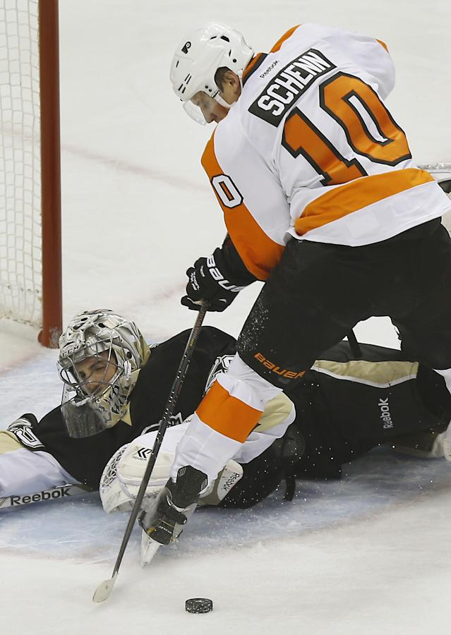Pittsburgh Penguins goalie Marc-Andre Fleury, left, makes a save on Philadelphia Flyers' Brayden Schenn (10) during the first period of an NHL hockey game on Sunday, March 16, 2014, in Pittsburgh. (AP Photo/Keith Srakocic)