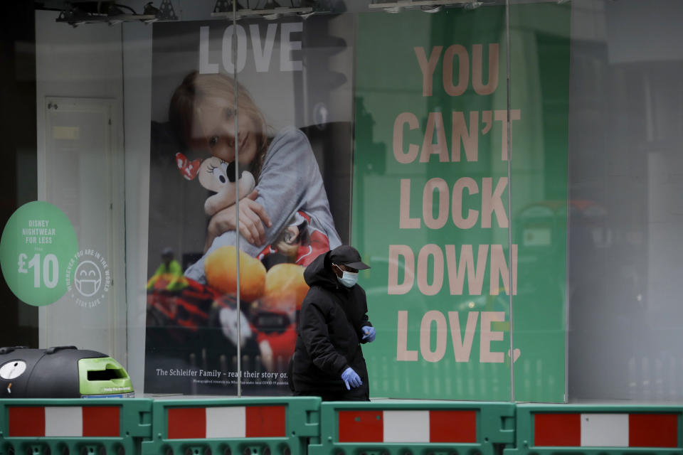 A man wearing a face mask and disposable gloves walks past the front window of the Primark clothing store on Oxford Street during England's second coronavirus lockdown, in London, Monday, Nov. 23, 2020. British Prime Minister Boris Johnson has announced plans for strict regional measures to combat COVID-19 after England's second lockdown ends Dec. 2, sparking a rebellion by members of his own party who say the move may do more harm than good. (AP Photo/Matt Dunham)