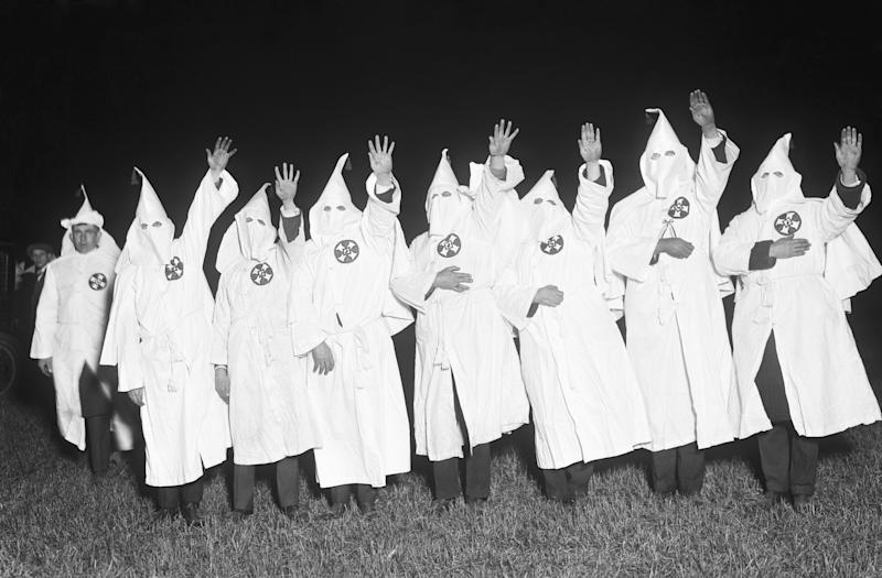 (Original Caption) Long Island, NY-Ku Klux Klan with hands raised in oath during night meeting.