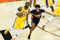 Los Angeles Lakers forward LeBron James, left, drives as Phoenix Suns forward Cameron Johnson defends during the second half of Game 5 of an NBA basketball first-round playoff series, Tuesday, June 1, 2021, in Phoenix. (AP Photo/Matt York)