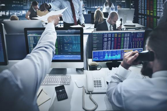 Two brokers reviewing computer screens full of financial data.