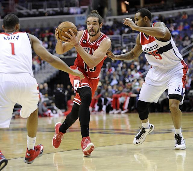 Chicago Bulls center Joakim Noah, center, drives to the basket against Washington Wizards' Trevor Ariza (1) and Trevor Booker (35) during the first half of an NBA basketball game, Saturday, April 5, 2014, in Washington. (AP Photo/Nick Wass)