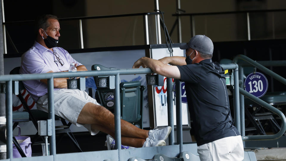 Colorado Rockies owner Dick Monfort, left, sits on the main concourse and talks with general manager Jeff Bridich as the baseball team practices Sunday, July 12, 2020, in Denver. (AP Photo/David Zalubowski)