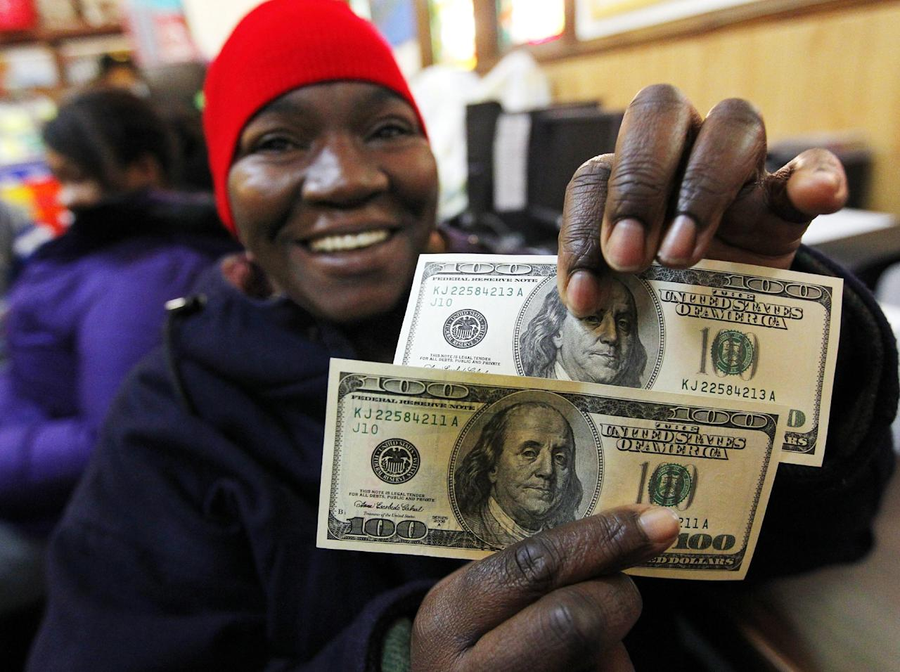 Charlotte Muhammad holds up two $100 dollar bills she got from Secret Santa, at St. Joseph's Social Service Center in Elizabeth, N.J., Thursday, Nov. 29, 2012. The wealthy philanthropist from Kansas City, Mo. known as Secret Santa distributed $100 dollar bills to needy people at St. Joseph's and other locations in Elizabeth. (AP Photo/Rich Schultz)