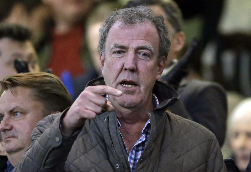 "FILE - In this Wednesday, March 11, 2015 file photo TV host Jeremy Clarkson gestures as he takes his place in the stands before the Champions League round of 16 second leg soccer match between Chelsea and Paris Saint Germain at Stamford Bridge stadium in London. Clarkson, the former host of hit BBC auto show ""Top Gear,"" has apologized and paid an undisclosed sum to a producer he punched in an off-set altercation it was reported on Wednesday, Feb. 24, 2016. Clarkson was fired in March 2015 after hitting Oisin Tymon during a dispute at the end of a day's filming. (AP Photo/Matt Dunham, File)"