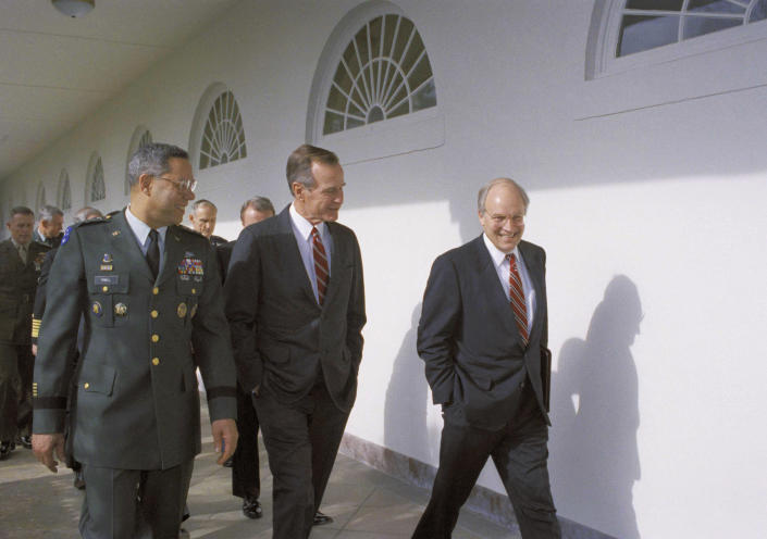 <p>President George H.W. Bush, center, talks to Defense Secretary Dick Cheney, right, as Joint Chiefs Chairman Gen. Colin Powell, left, looks on at the White House, on Jan. 16, 1992, in Washington, D.C. The president was escorting members of the Joint Chiefs of Staff and other Pentagon officials to a luncheon on the first anniversary of the start of the Gulf War. (Photo: Dennis Cook/AP) </p>