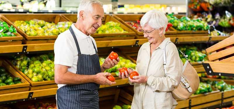 Elderly couple checking out produce in a grocery store.