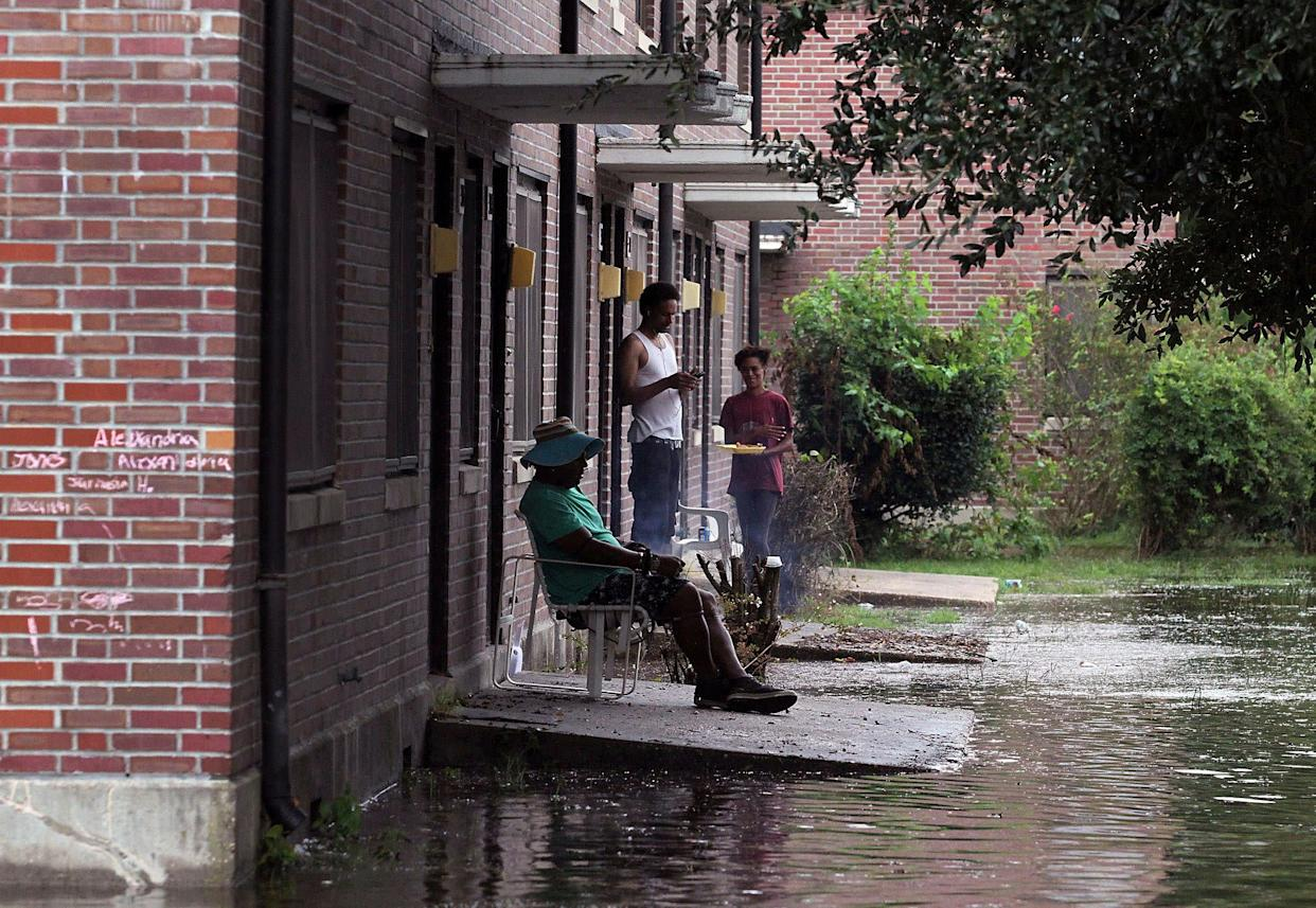 Residents at Trent Court Apartments wait out the weather as rising waters get closer to their doors in New Bern on Thursday.
