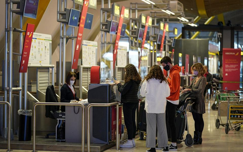 Passengers use a check-in counter in the departures hall at Madrid Barajas airport - Paul Hanna/Bloomberg