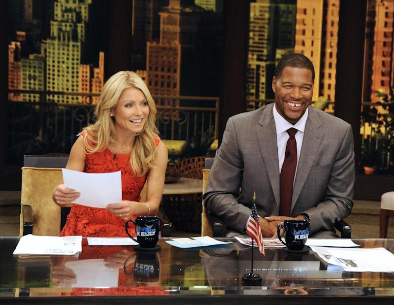 """This undated photo shows former football player Michael Strahan, right, and host Kelly Ripa during Strahan's guest-host appearance on """"Live! with Kelly,"""" earlier this year in New York. Strahan is getting a permanent job in morning television as Kelly Ripa's co-host. Strahan replaces Regis Philbin on the syndicated """"Live! With Kelly"""" show, adding his name to the title. The gap-toothed former New York Giant is currently a host of """"Fox NFL Sunday."""" He was one of several men to get tryouts with Ripa as the show rotated several potential replacements since Philbin left last November. (AP Photo/Disney-ABC Domestic TV, Donna Svennevik)"""