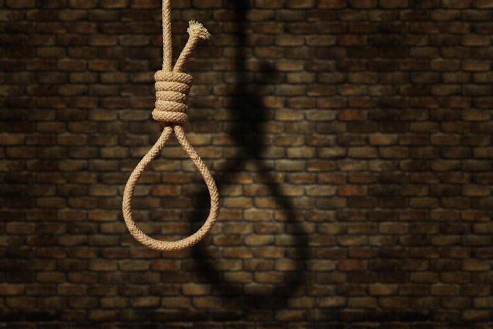 suicide concept. noose with shadow on dark wall background