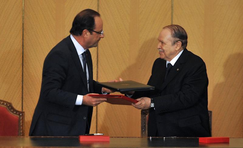 French President Francois Hollande, left and Algerian President Abdelaziz Bouteflika exchange signed contracts in Algiers, Wednesday, Dec. 19, 2012. Commercial contracts,  particularly in the food and agriculture areas, were signed along with an agreement to an assembly plant of Renault vehicles, near Oran, Algeria. Hollande arrived Wednesday on a state visit to Algeria, hoping for a clean start in relations after a half-century of tensions with this North Africa nation, once the French empire's most prized colony. (AP Photo/Djarboub Sidali )