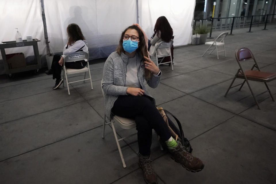 Angela Margos, a tourist on her way to visit Maui, sits in a waiting area for test results at the SFO COVID-19 rapid testing site before a United Airlines flight to Hawaii at San Francisco International Airport in San Francisco, Thursday, Oct. 15, 2020. Coronavirus weary residents and struggling business owners in Hawaii will be watching closely as tourists begin to return to the islands on Thursday without having to self-quarantine upon arrival. (AP Photo/Jeff Chiu)