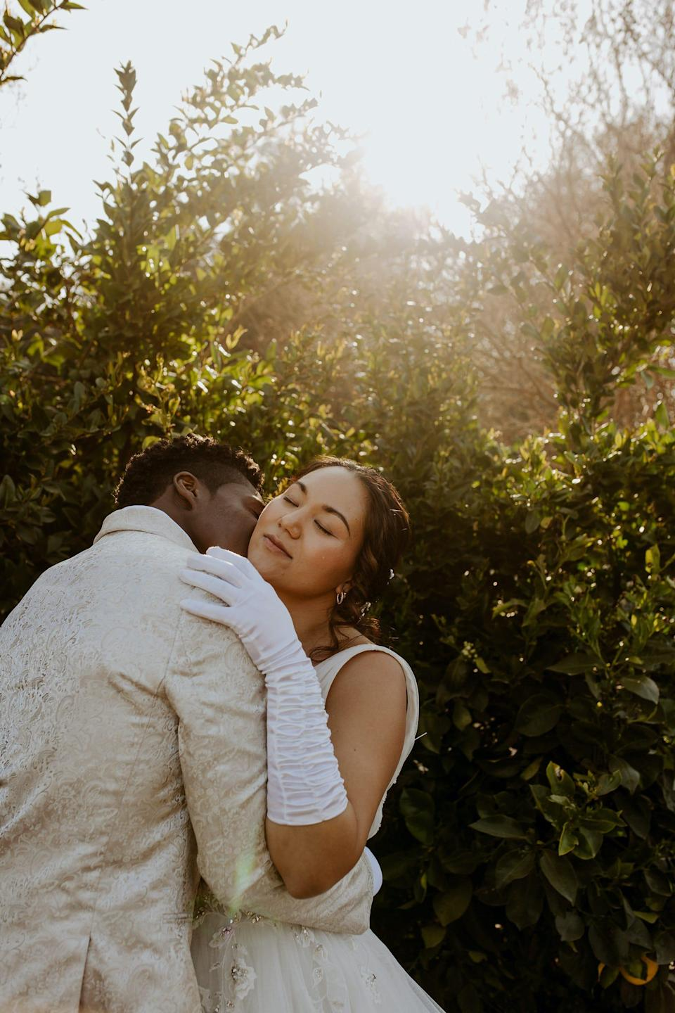 A bride and groom embrace in front of trees.