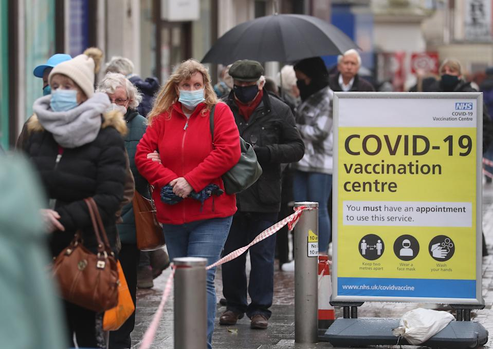 People queue in bad weather to enter a COVID-19 vaccination centre in Folkestone, Kent, during England's third national lockdown to curb the spread of coronavirus. Picture date: Friday January 29, 2021.