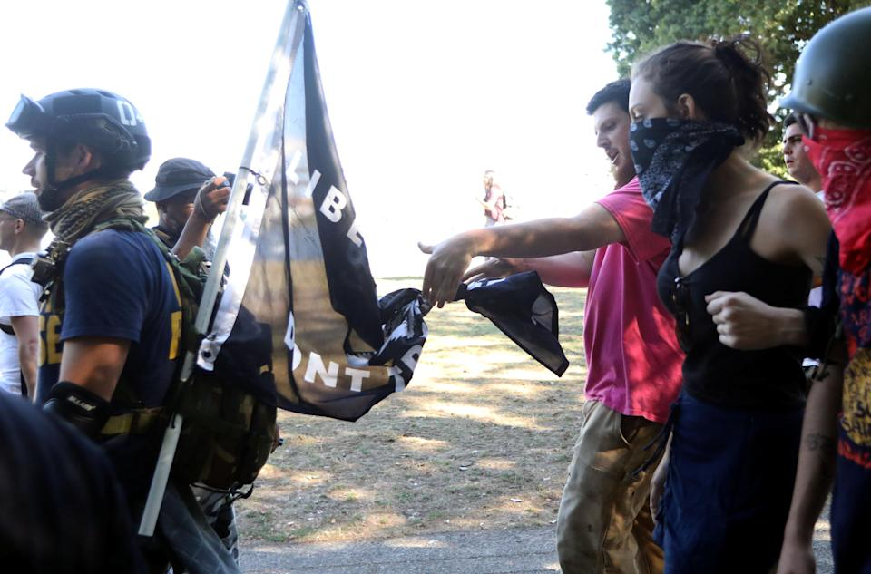 <p>Counterprotesters, right, tie a knot in a flag carried by a right-wing supporter of the Patriot Prayer group during a rally in Portland, Ore., Aug. 4, 2018. (Photo: Jim Urquhart/Reuters) </p>